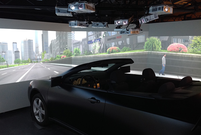 Car in front of screen with street projected in front of it