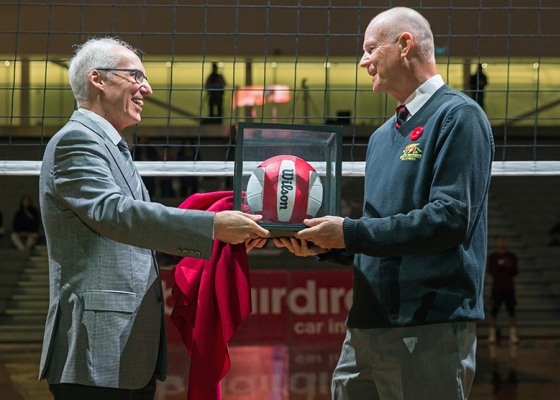 Larry Pearson accepting volleyball in glass box from President Vaccarino