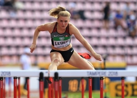 girl jumping over hurdle